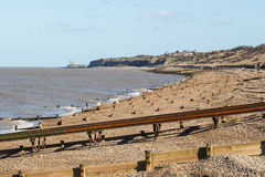 Herne Bay beach and Reculver Towers. Herne Bay beach with its rows of wooden water breaker, groynes, a slipway and Reculver Towers Stock Images
