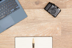Hero Header image of tidy artist desktop. Tidy organized desk top with laptop, camera and notebook with pen on an oak wooden table for designer workspace Royalty Free Stock Photography