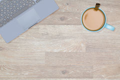 Hero Header image of tidy desktop with mug of coffee. Tidy organized desk top with laptop and cup of coffee or tea on an oak wooden table for designer workspace Stock Photos