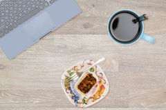 Hero Header image of tidy desktop with snack. Tidy organized desk top with laptop, cup of coffee and fruitcake on an oak wooden table for designer workspace Stock Photography