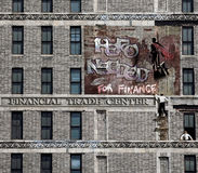 Hero needed. On a building, above a financial trade center, a graffiti representing a superhero watching the city, with the text hero needed Stock Photo