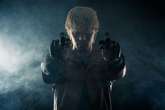 Hero with pistols in hands aiming. Smoke Royalty Free Stock Images