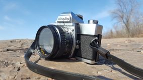 Minolta SRT 102 with 50mm f1.7 Rokkor Lens on Rocks. A hero shot, 3/4 view of an old manual SLR film camera sitting on rocks against a blue sky in late morning Royalty Free Stock Images