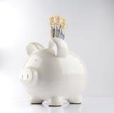 Hero shot of white piggy bank with three Australian 50 dollar ba. Nknotes  on white Stock Image