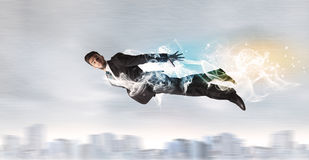 Hero superman flying above city with smoke left behind Royalty Free Stock Photography
