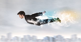 Hero superman flying above city with smoke left behind Royalty Free Stock Images