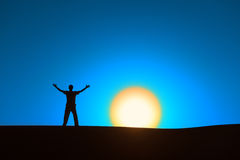 Heroic achievement by men. Man at blue background with big sun under horizon with heroic achievement gesture Royalty Free Stock Photo