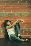 Heroin chic. Androgyny female model in Heroin chic style near brick wall. Old style tinted image Stock Photos