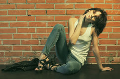 Heroin chic. Androgyny female model in Heroin chic style near brick wall. Old style tinted image Stock Images