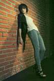 Heroin chic. Androgyny female model in Heroin chic style near brick wall. Old style tinted image Stock Photography