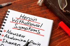 Heroin withdrawal written on a note. Drugs addiction concept Royalty Free Stock Photo