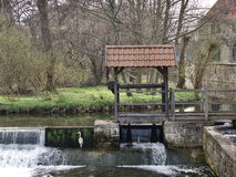 Heron fishing at a scenic rural weir. With water cascading over the spillway and an old stone mill building in the background Stock Photography