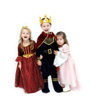 A Heros Back in Town. Three children dressup as King, Queen and Princess for Halloween.  Little Princess is leaning against her King and the Queen is laughing at Stock Image