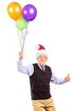 Herr, der Ballone anhält und Daumen aufgibt Stockfotografie