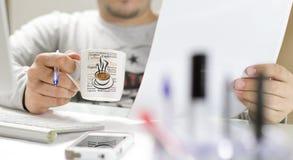 Herr, der Kaffee beim Ablesen ihrer Anmerkungen trinkt lizenzfreies stockbild