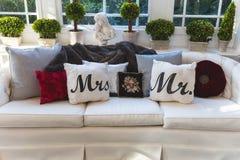 Herr och fru kudde på en soffa på ett bröllopmottagande arkivfoto