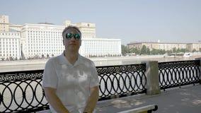Herr von mittlerem Alter in einem weißen Hemd steht auf der Ufergegend still stock video footage