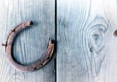 Herradura oxidada vieja en el tablero de madera del vintage Imagenes de archivo