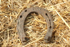 Herraduras oxidadas en un fondo de la paja - escena rústica en un estilo rural Herradura vieja del hierro - símbolo de la buena s Fotos de archivo