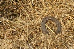 Herraduras oxidadas en un fondo de la paja - escena rústica en un estilo rural Herradura vieja del hierro - símbolo de la buena s Foto de archivo