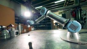 Herramienta cibernética que trabaja en una tabla de la fábrica en una instalación metrajes