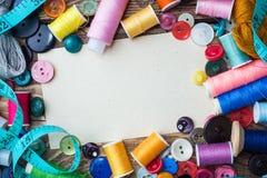 Herramienta de costura para la costura, los hilos coloreados centímetro y los botones con un par de tijeras en la tabla Copie el  foto de archivo libre de regalías