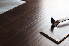Herramienta de la barra de palanca con el nuevo suelo laminado imagen de archivo