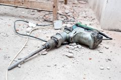 Herramienta de la construcción, el martillo perforador con ruina de la demolición Imágenes de archivo libres de regalías