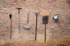 Herramienta del instrumento del granjero que cuelga en el brickwall Imágenes de archivo libres de regalías