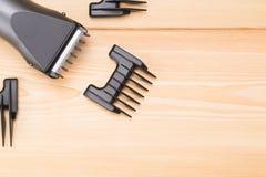 Herramienta del ` s del peluquero para el corte del pelo con diversos accesorios en una tabla de madera Imagen de archivo libre de regalías