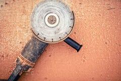 Herramienta eléctrica de la amoladora de ángulo o sierra portátil usada para cortar o acanalar el acero, el hierro, el hormigón u Imagen de archivo
