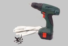 Herramienta eléctrica del screwdriwer con los guantes y los tornillos Fotografía de archivo libre de regalías