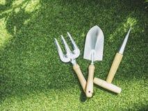 Herramienta que cultiva un huerto en fondo al aire libre de la hierba verde Imágenes de archivo libres de regalías