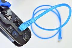 Herramienta que prensa azul con un cable de la red de ordenadores Imágenes de archivo libres de regalías