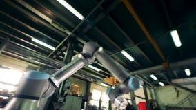 Herramienta robótica moderna que gira en una tabla, trabajando en una planta metrajes