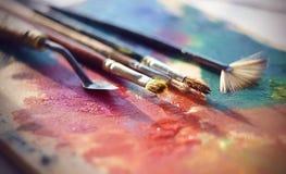 Herramientas artísticas para crear una mentira de la imagen en la paleta con la pintura de aceite fotografía de archivo libre de regalías