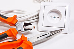 Herramientas, cable y enchufe de pared del electricista Foto de archivo
