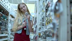 Herramientas de compra de la mujer en tienda almacen de metraje de vídeo