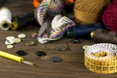 Herramientas de costura en un fondo de madera Foto de archivo