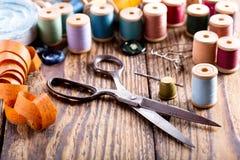 Herramientas de costura: tijeras, bobinas con el hilo y agujas Imágenes de archivo libres de regalías