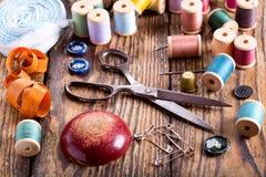 Herramientas de costura: tijeras, bobinas con el hilo y agujas Foto de archivo