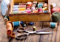 Herramientas de costura: tijeras, bobinas con el hilo y agujas Foto de archivo libre de regalías
