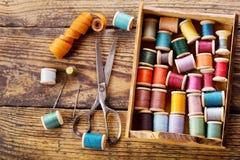 Herramientas de costura: tijeras, bobinas con el hilo y agujas Fotos de archivo