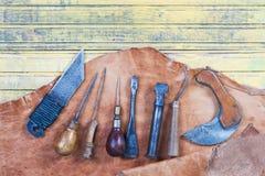 Herramientas de cuero del arte en un fondo de madera Escritorio de cuero del trabajo de los craftmans Pedazo de piel y de herrami Foto de archivo