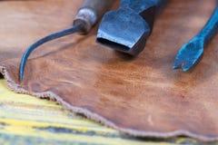 Herramientas de cuero del arte en un fondo de madera Escritorio de cuero del trabajo de los craftmans Pedazo de piel y de herrami Fotografía de archivo libre de regalías