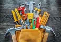 Herramientas de cuero del edificio del toolbelt en el tablero de madera directamente arriba Imagenes de archivo