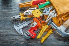 Herramientas de cuero del edificio del toolbelt en la opinión superior del fondo de madera Foto de archivo