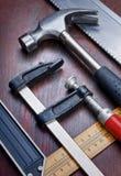 Herramientas de DIY sobre un panel de madera Imagenes de archivo