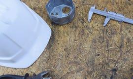 herramientas de funcionamiento de un constructor en un emplazamiento de la obra, mintiendo en un tabl de escritorio de madera Foto de archivo