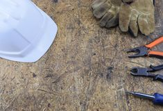 Herramientas de funcionamiento de un constructor en un emplazamiento de la obra, mintiendo en una tabla de escritorio de madera Foto de archivo libre de regalías